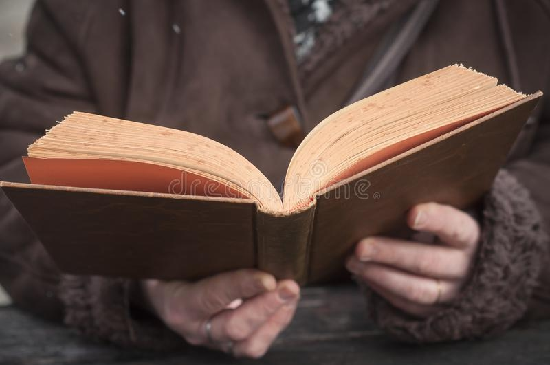 Kvinna som läser en gammal bok i utomhus- arkivbilder