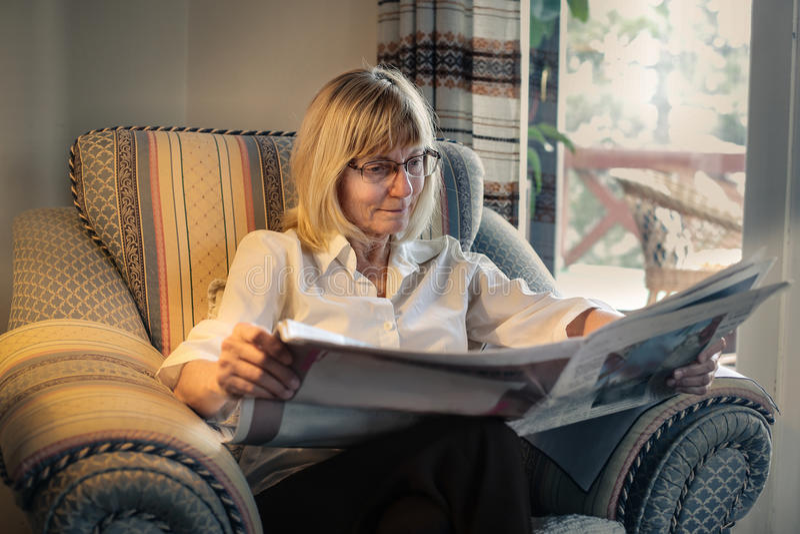 Kvinna som läser en tidning royaltyfri fotografi