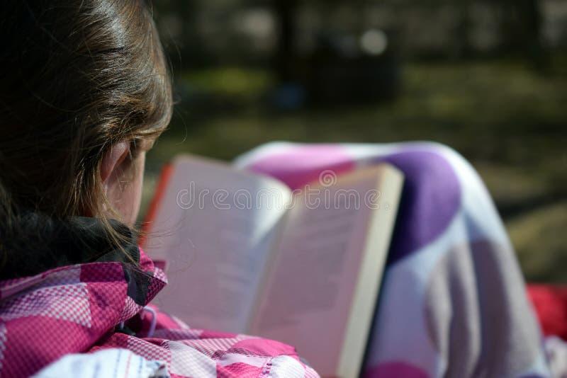 Kvinna som läser en utomhus- bok royaltyfria bilder