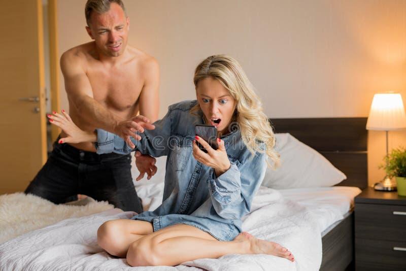 Kvinna som läser hennes meddelanden för fusk för man` s på hans telefon arkivbilder