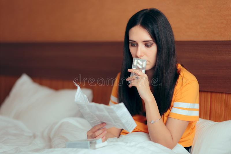 Kvinna som läser medicinbroschyren, innan att ta piller royaltyfri bild
