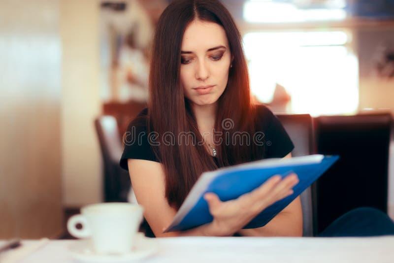 Kvinna som läser viktiga dokument i en restaurang arkivfoto