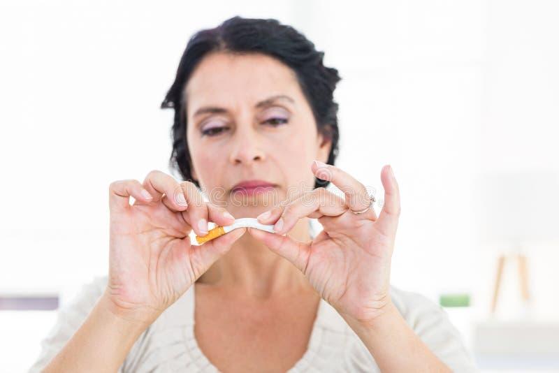 Kvinna som låser fast hennes cigarett royaltyfria bilder