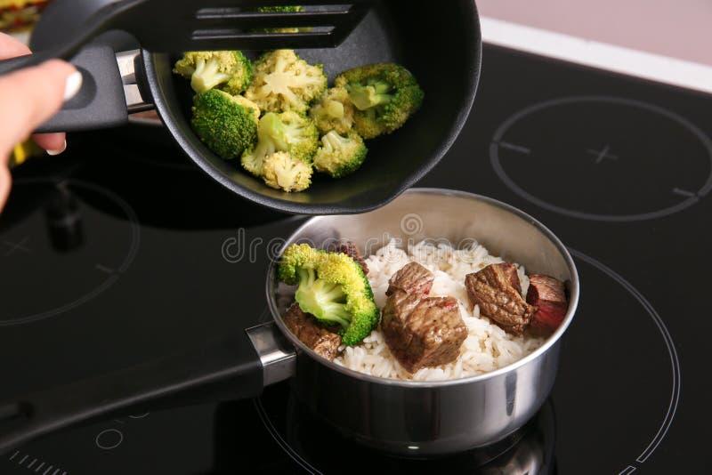 Kvinna som lagar mat ris med kött och broccoli i kök royaltyfria bilder