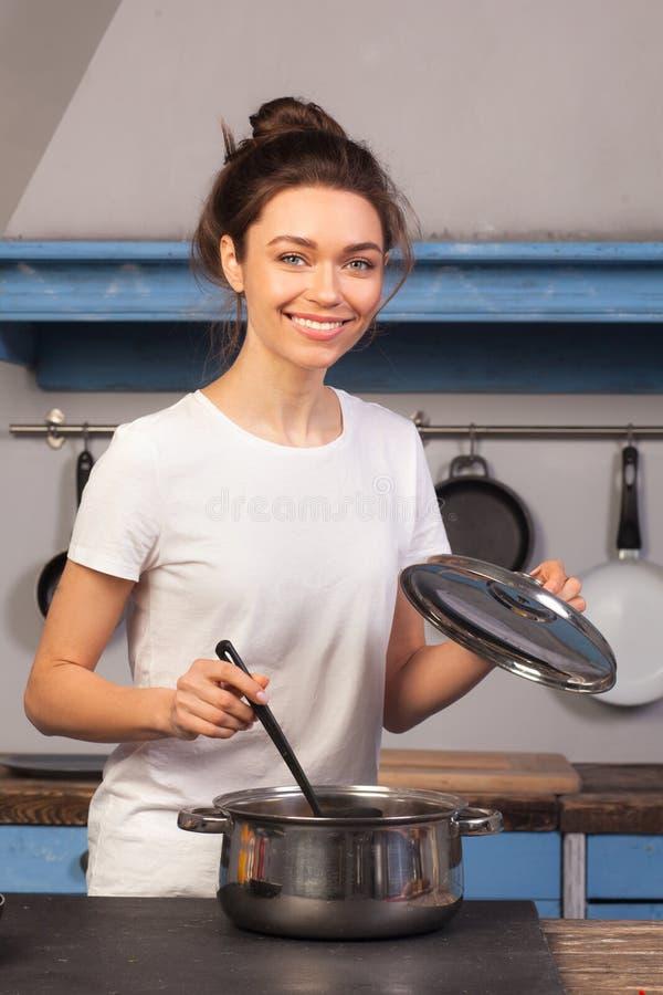 Kvinna som lagar mat soppa på köket royaltyfria foton