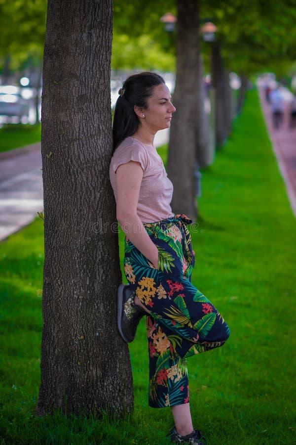 Kvinna som leanning på träd royaltyfria bilder