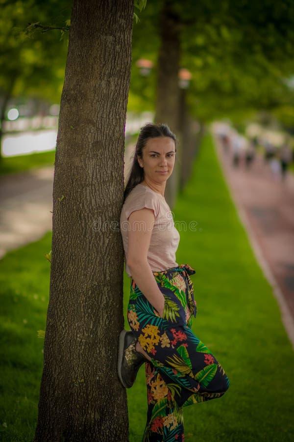 Kvinna som leanning på träd arkivbilder