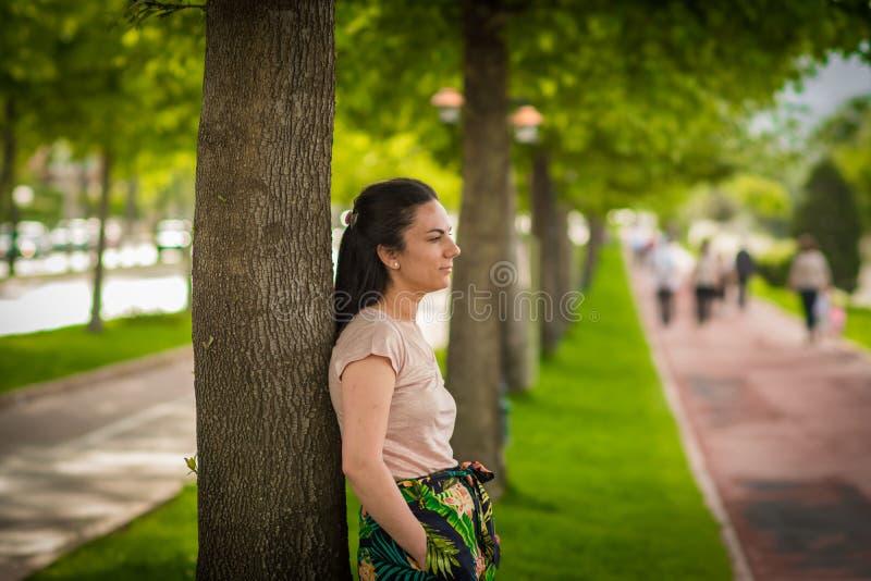 Kvinna som leanning på träd arkivfoto