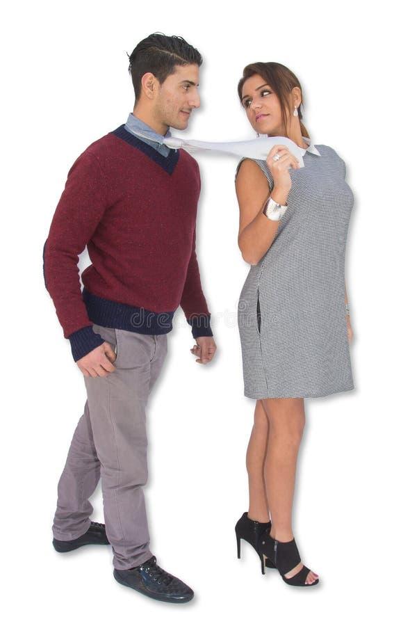 Kvinna som leder en man, genom att dra honom vid hans slips royaltyfria foton