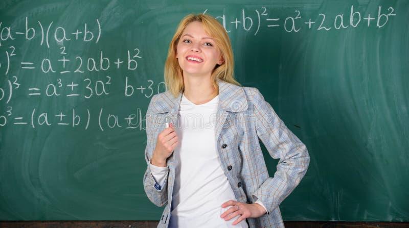 Kvinna som ler bakgrund för svart tavla för utbildareklassrum Arbetsförhållanden som presumtiva lärare måste betrakta royaltyfri bild