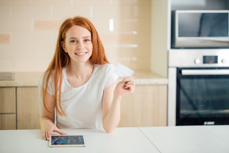 Kvinna som ler, genom att använda minnestavlaskärm- och innehavkreditkorten i vardagsrum royaltyfria bilder