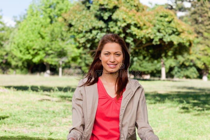 Kvinna som ler i ett område som omges av gräs arkivbild
