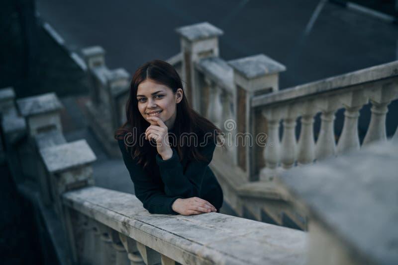 Kvinna som ler, kvinna som knäppas fast på räcket, kvinna på trappuppgångbakgrunden arkivfoton
