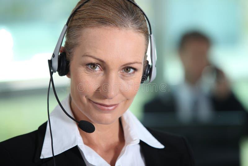 Kvinna som ler med hörlurar med mikrofon arkivfoton