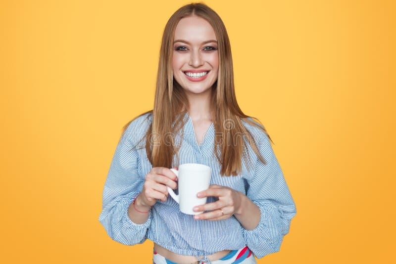 Kvinna som ler med koppen i studio royaltyfri fotografi