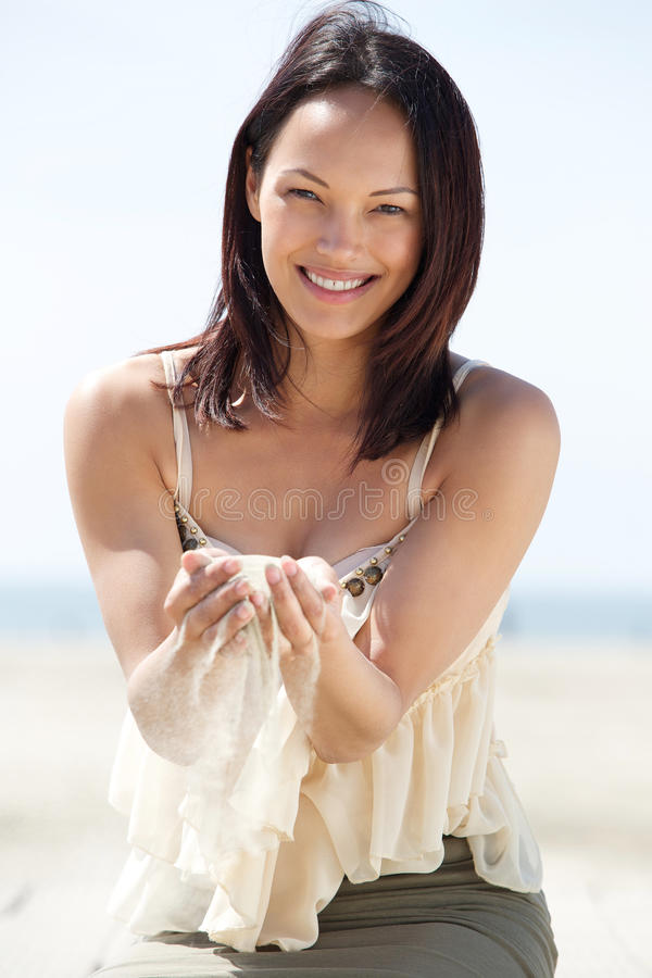 Kvinna som ler med sand som faller till och med fingrar arkivfoto