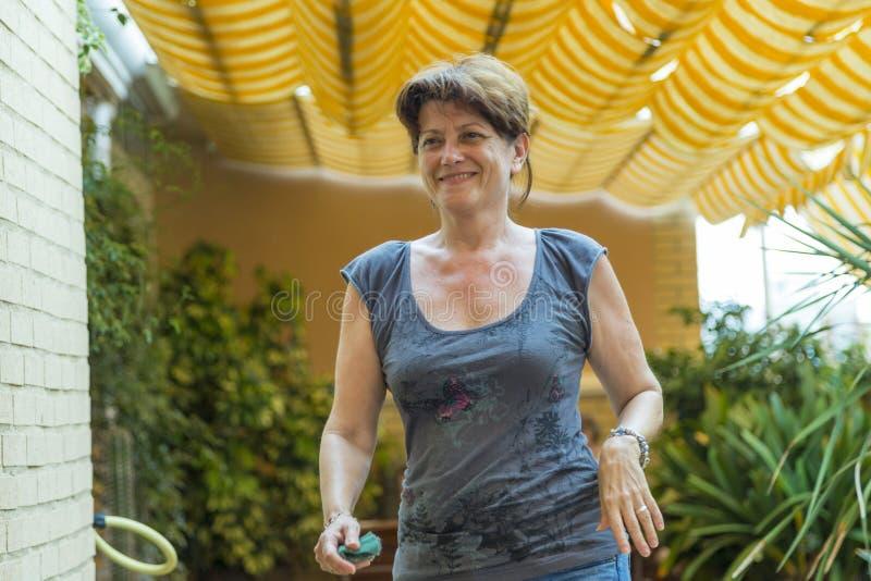 Kvinna som ler, medan gå på hennes terrass arkivfoton
