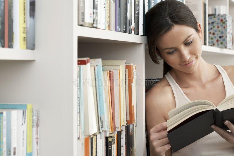 Kvinna som ler, medan läsa vid bokhyllor royaltyfri foto