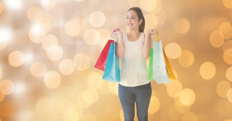 Kvinna som ler, medan rymma shoppingpåsar över bokeh royaltyfri bild