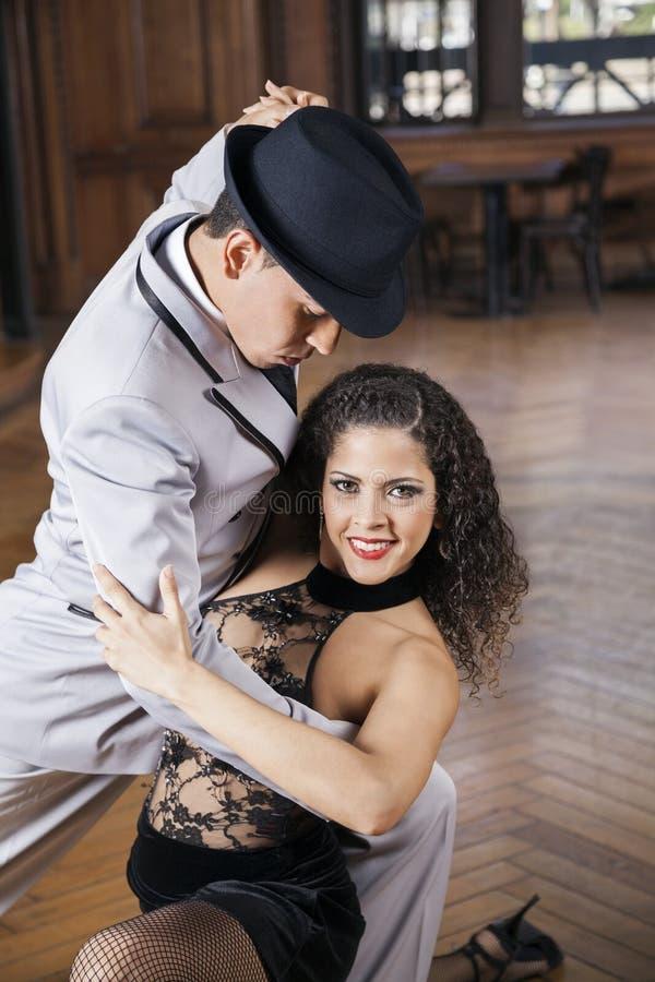 Kvinna som ler, medan utföra tango med mannen royaltyfri fotografi