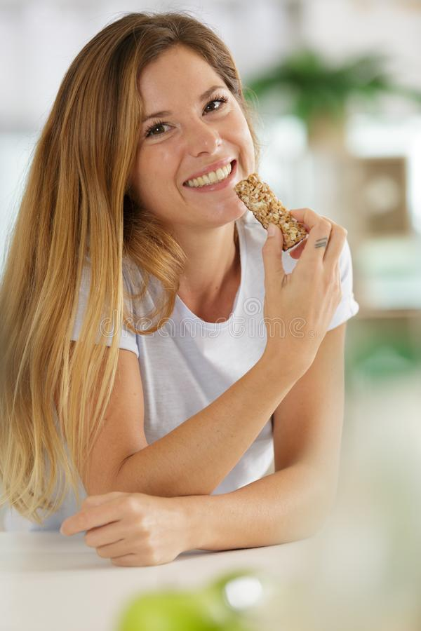 Kvinna som ler och går att äta mysli royaltyfri fotografi