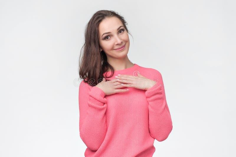 Kvinna som ler och håller handen på hennes bröstkorg som är glad att motta komplimang arkivbild