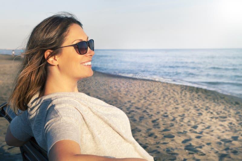 Kvinna som ler och kopplar av på det iklädda fredsammanträdet för hav på bänken på stranden solglasögon royaltyfria bilder