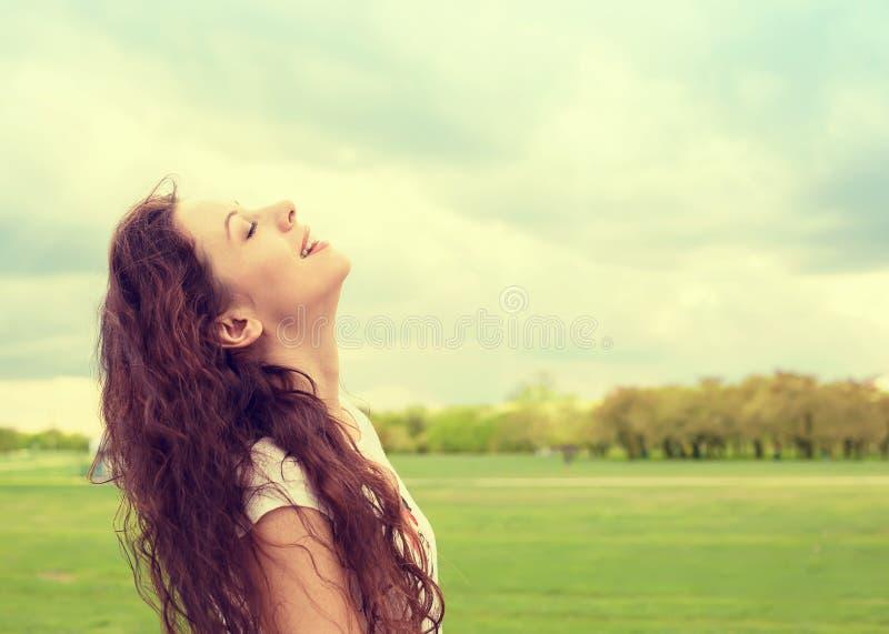 Kvinna som ler se upp till blå himmel som firar tycka om frihet arkivfoton