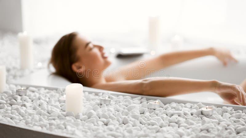Kvinna som ligger i bad med skum och stearinljus royaltyfria foton