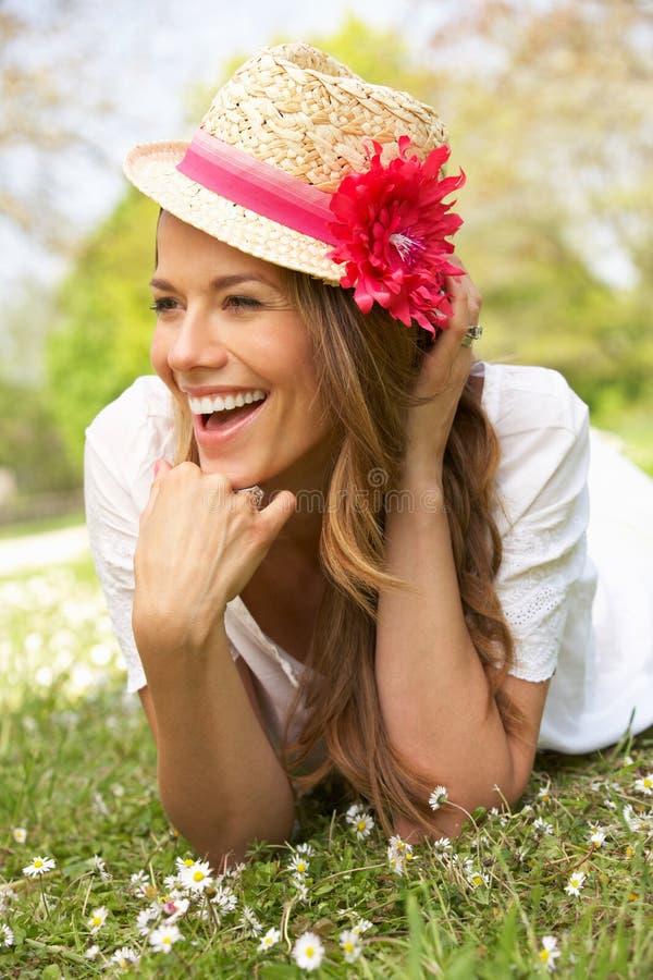 Kvinna som ligger i fält av sommarblommor royaltyfri foto