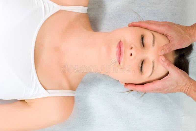 Kvinna som ligger motta ner den head massagen arkivfoto