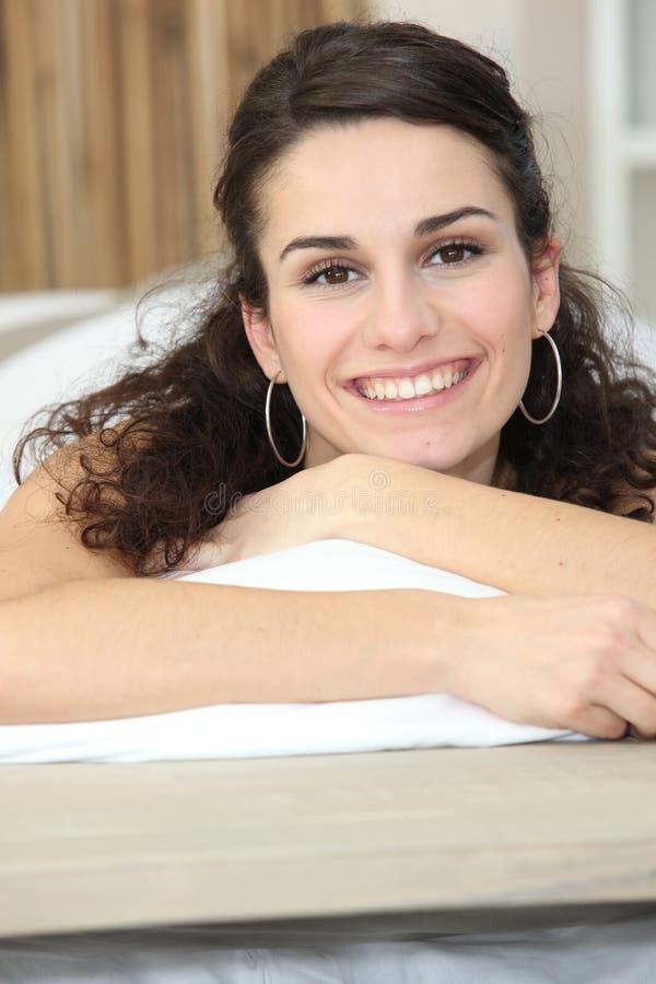 Kvinna som ligger på att le för underlag arkivfoton