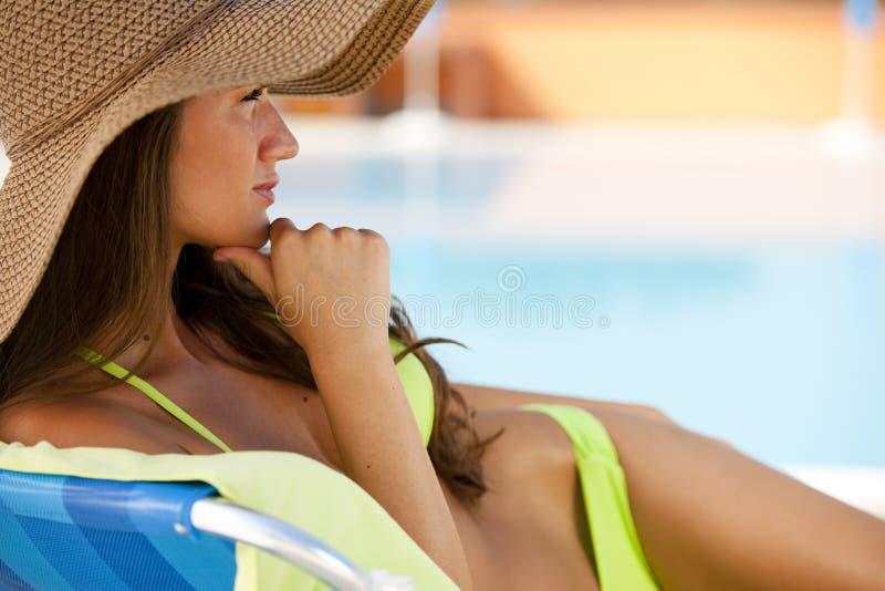Kvinna som ligger på deckchair vid swimmingen-pool royaltyfria bilder