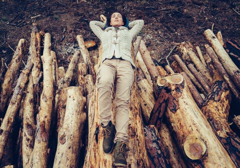 Kvinna som ligger på den avverkade trädstammen arkivbilder