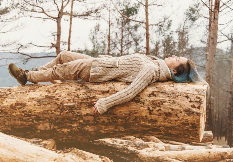 Kvinna som ligger på den utomhus- trädstammen arkivfoton