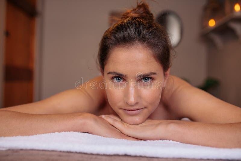 Kvinna som ligger på en massagetabell i wellnessmitt royaltyfri fotografi