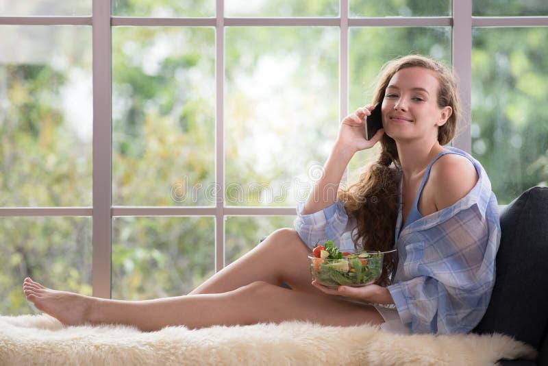 Kvinna som ligger på en soffa genom att använda smartphonen och innehavet en salladbunke royaltyfria foton