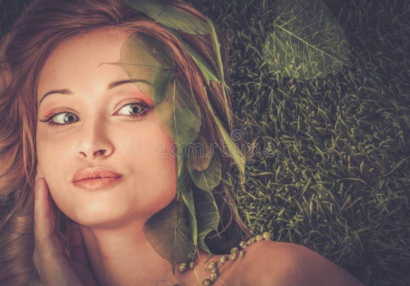 Kvinna som ligger på ett nytt vårgräs royaltyfria bilder