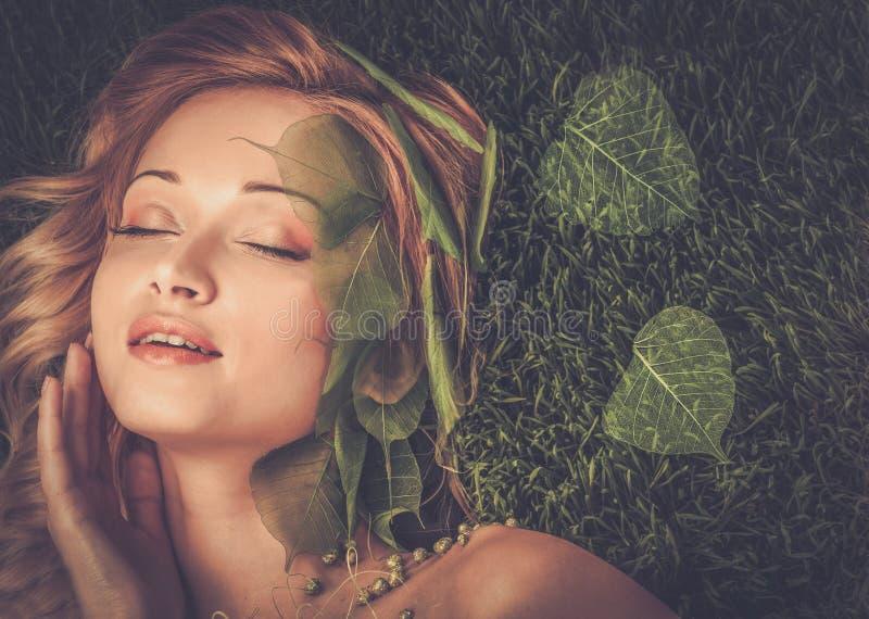 Kvinna som ligger på ett nytt vårgräs royaltyfria foton