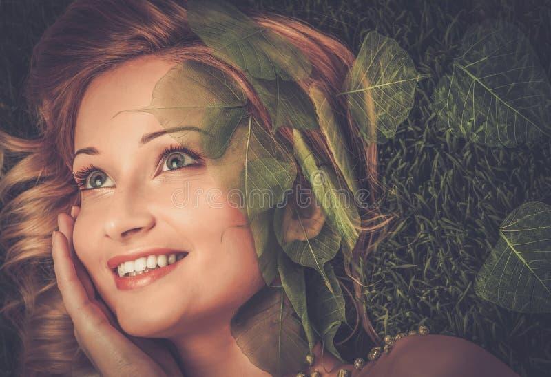 Kvinna som ligger på ett nytt vårgräs arkivfoton
