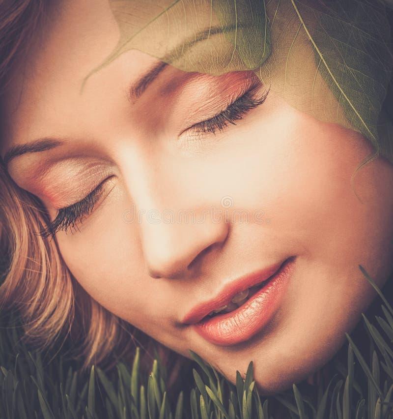 Kvinna som ligger på ett nytt vårgräs royaltyfri bild