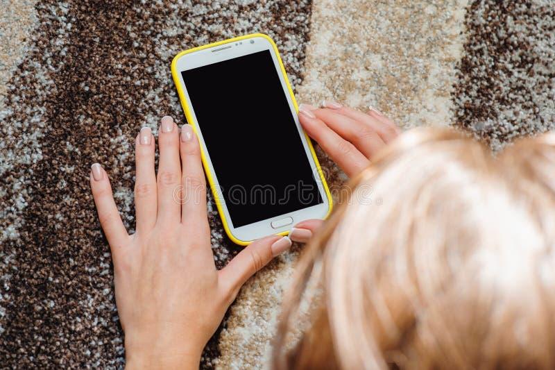 Kvinna som ligger på golvet med smartphonen arkivfoto