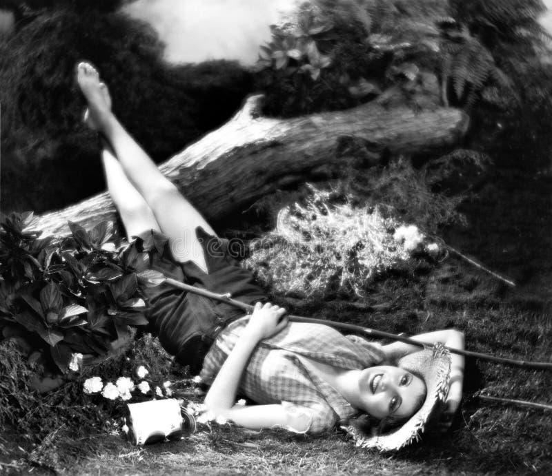 Kvinna som ligger på jordningen, och le (alla visade personer inte är längre uppehälle, och inget gods finns Leverantörgarantier  arkivfoto