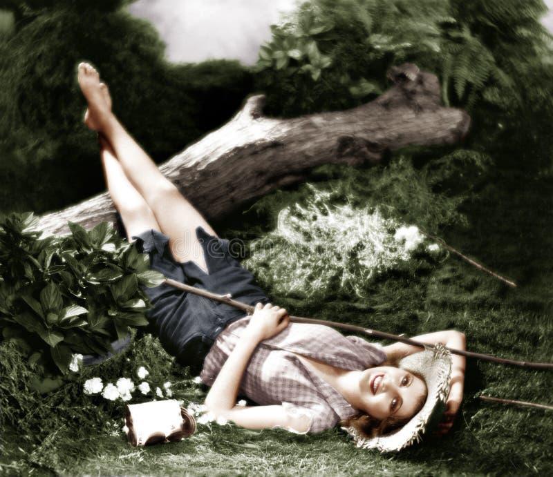 Kvinna som ligger på jordningen, och le (alla visade personer inte är längre uppehälle, och inget gods finns Leverantörgarantier  royaltyfri foto