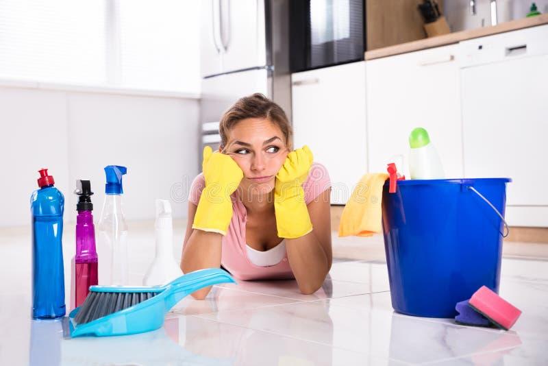 Kvinna som ligger på kökgolv och ser lokalvårdprodukter royaltyfria bilder