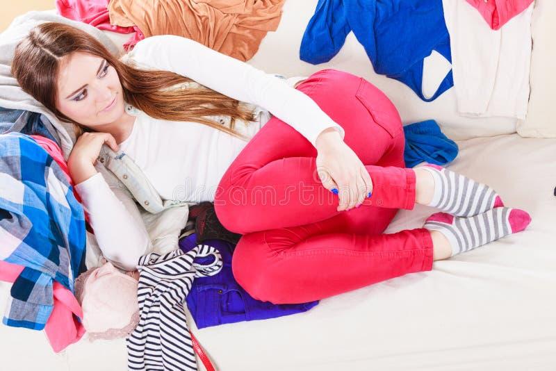 Kvinna som ligger på kläder Röra och oordning fotografering för bildbyråer