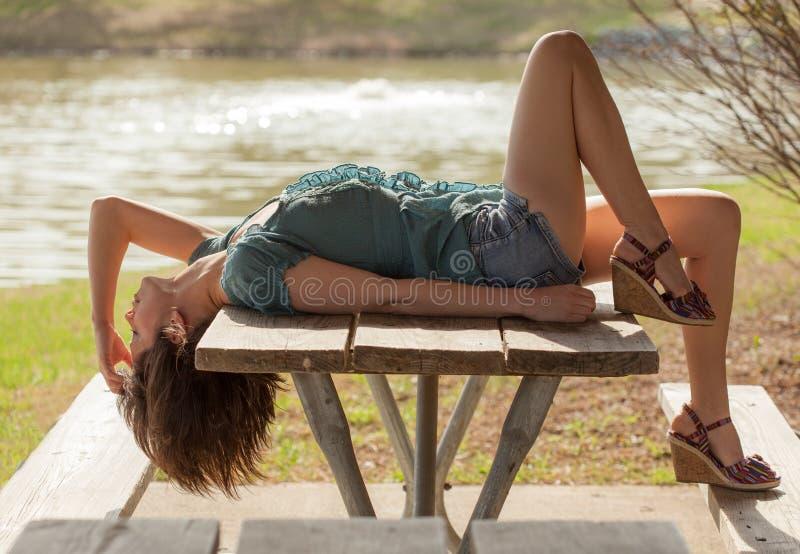Kvinna som ligger på picknicktabellen royaltyfri foto