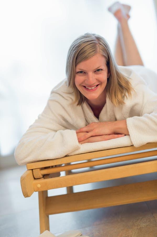 Kvinna som ligger på säng på brunnsorten royaltyfri fotografi