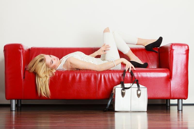 Kvinna som ligger på soffan som framlägger den vita påsen royaltyfria bilder