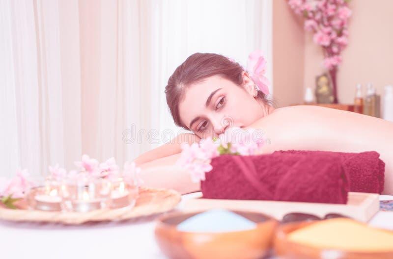 Kvinna som ligger på Spa massagesäng med brunnsortutrustning på förgrund royaltyfri fotografi